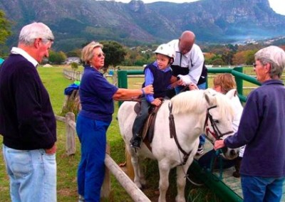 Volunteers helping a child onto a horse equine therapy for disabled children South Africa